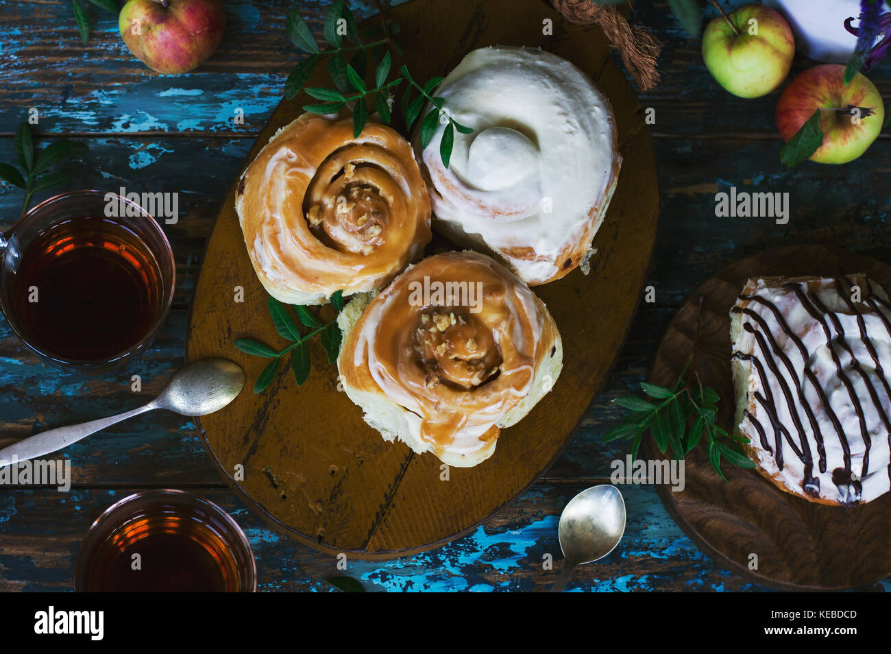 Fresh baked cinnamon rolls with frosting, apples and tea on the shabby background. View from top - Stock Image