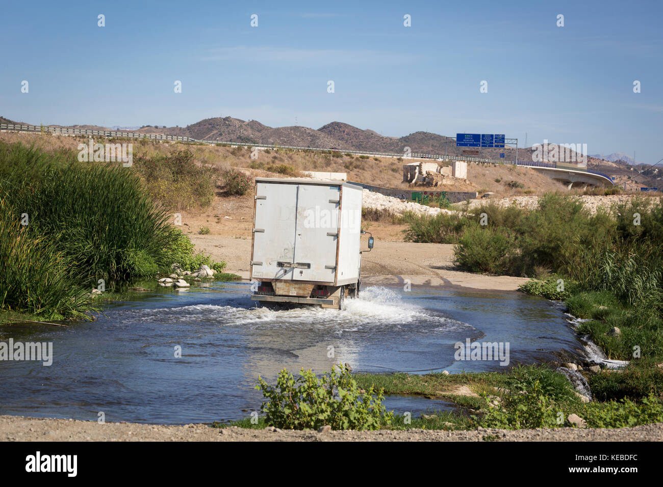 A river ford.  A ford is a shallow spot in a river or stream which permits traffic to drive across, or people to - Stock Image
