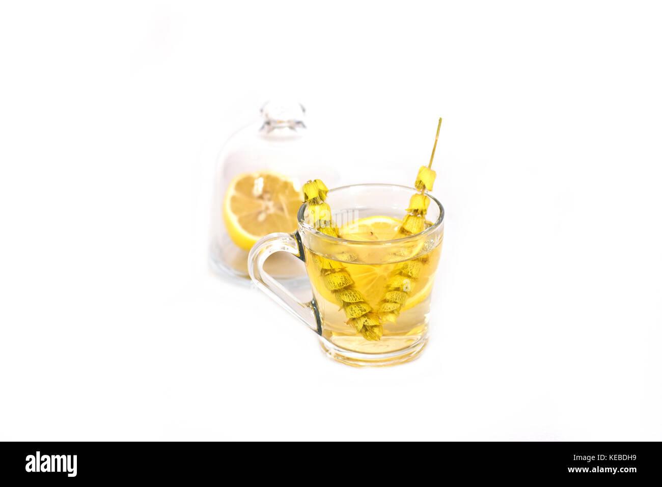 Hot tea with sage and lemon in the glass mug. Stock Photo