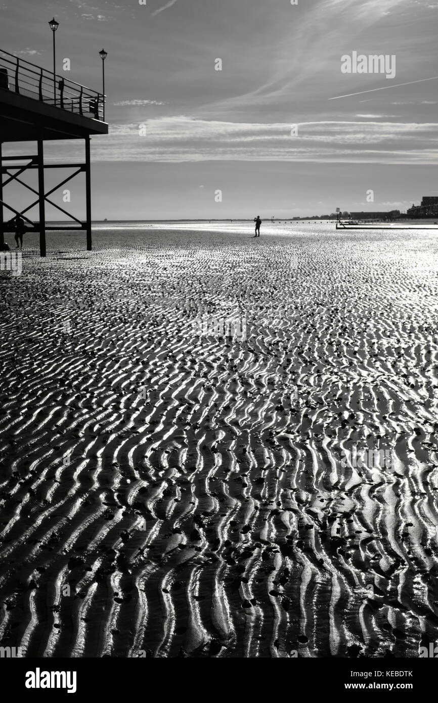 Cleethorpes seafront at low tide figures stand close to the pier - Stock Image