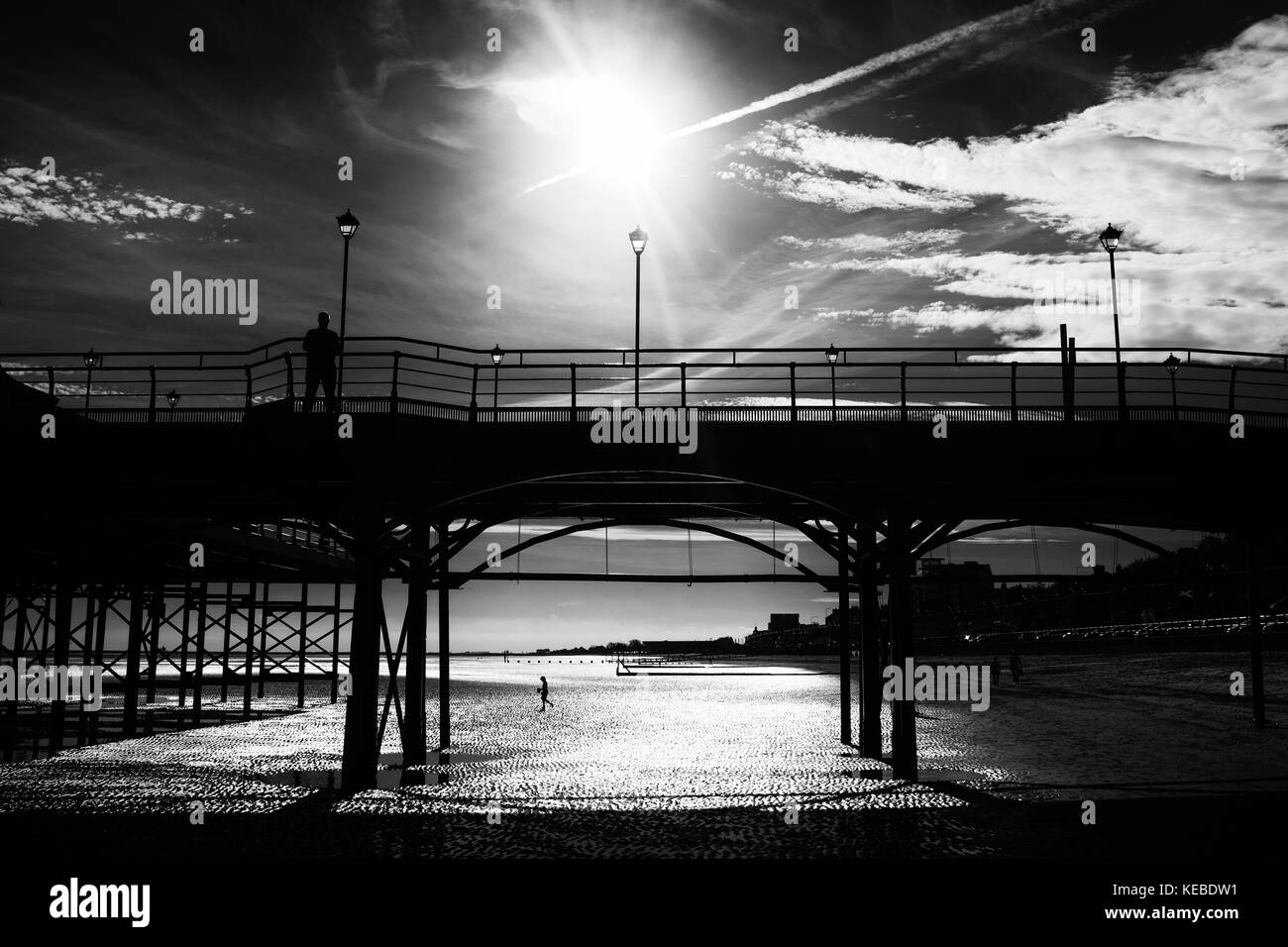 Shadowy adult figure stands on a silhouetted Cleethorpes Pier, a child with a bucket walks on wet sand in background. - Stock Image