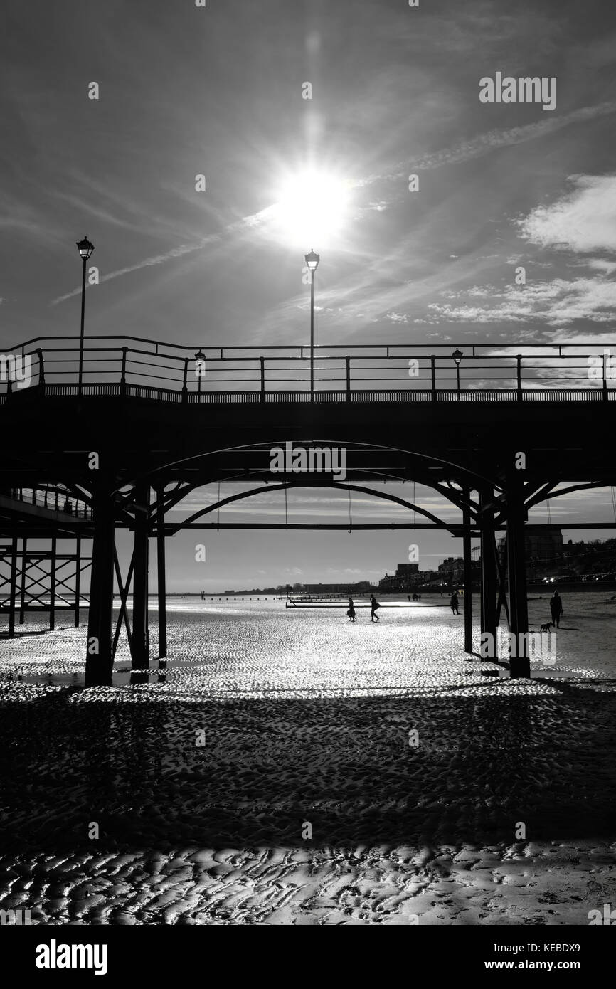 Tourists walking out to waters edge past silhouetted Cleethorpes pier - Stock Image