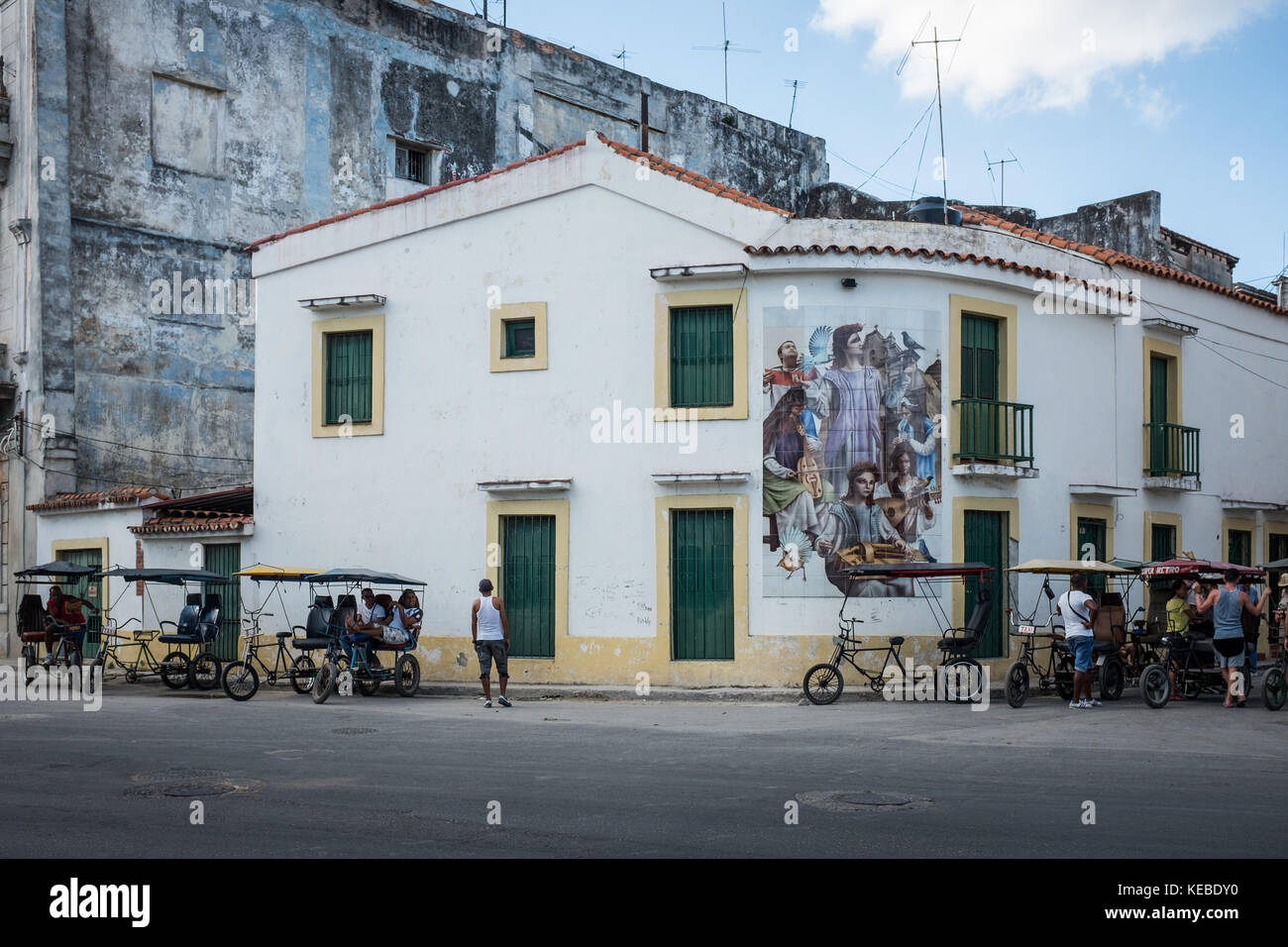 Bicitaxi riders gather next to building with mural painted architecture, Havana, Cuba - Stock Image
