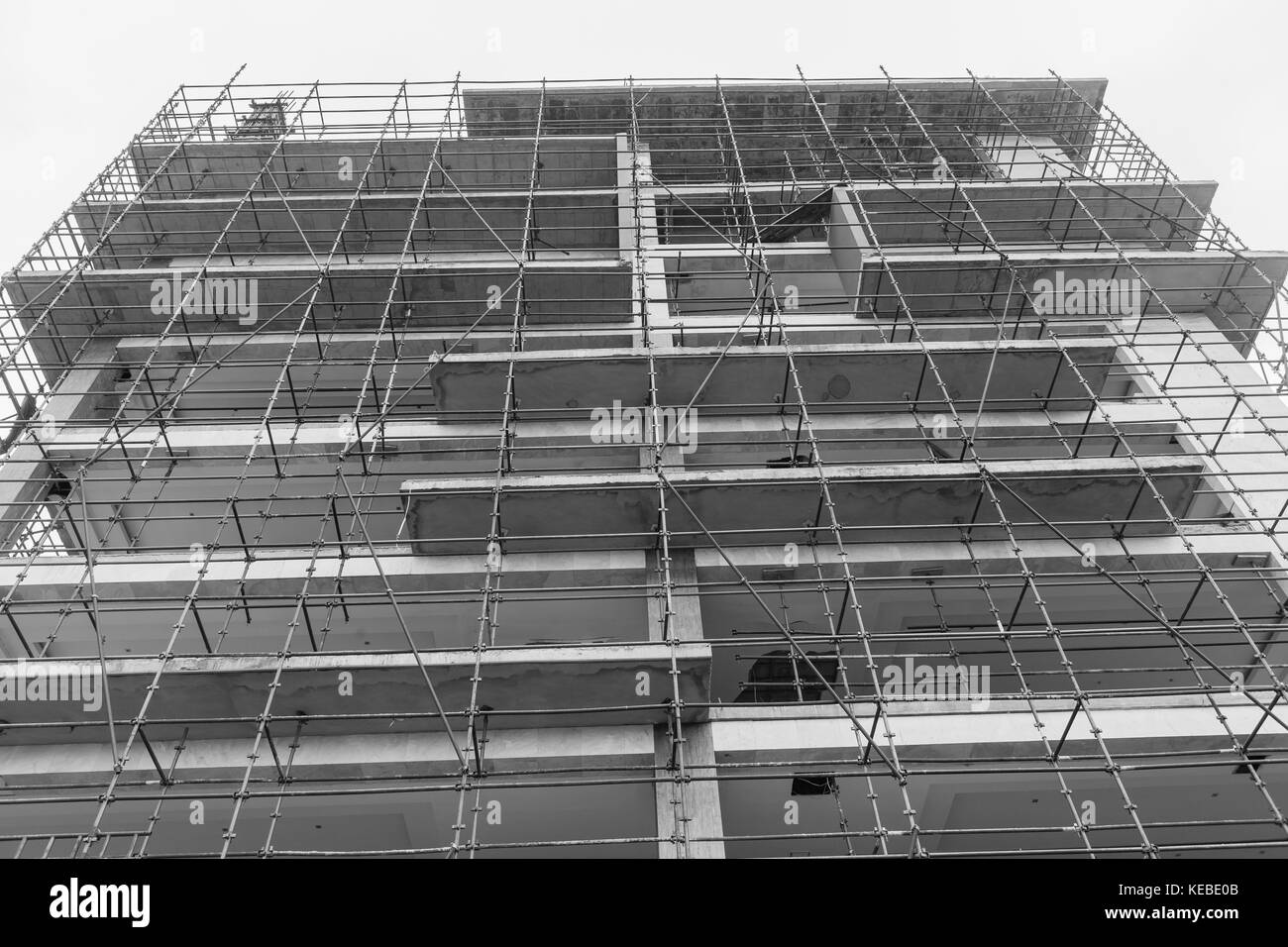 Building construction in progress of floors  apartments raw state of concrete and steel scaffolding upward black - Stock Image