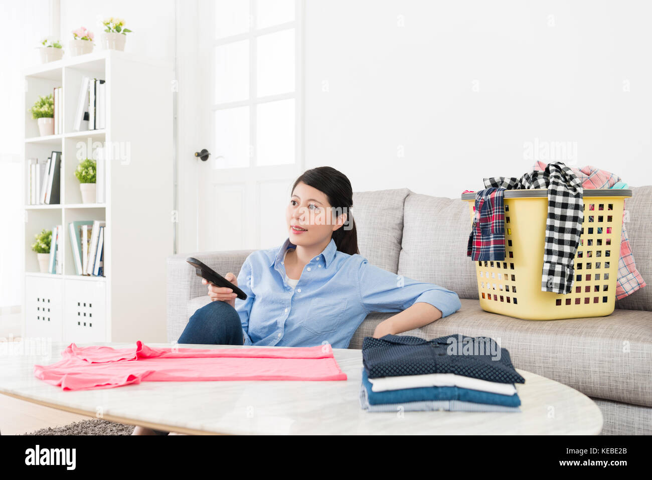 young pretty housewife folding family messy clothing in living room ...