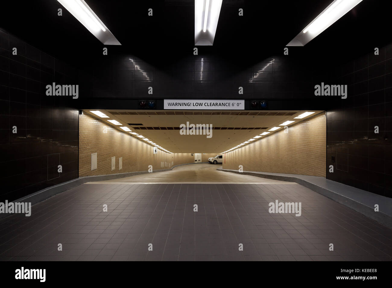 entrance with low clearance to an underground parking garage - Stock Image