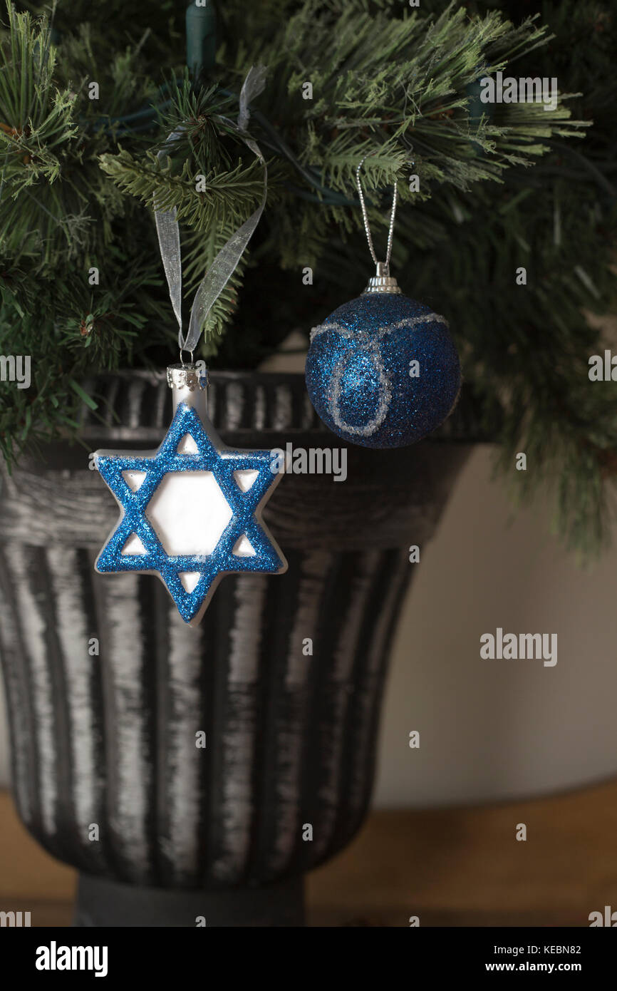 Hanukkah and Christmas decorations side by side on Christmas tree - Stock Image