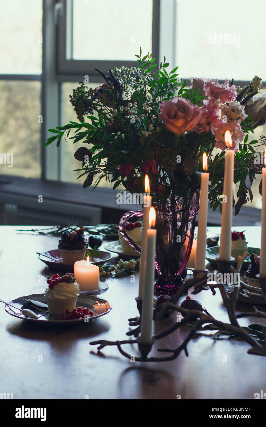 The beautiful festive table with rustic bouquet, dessert and candles - Stock Image