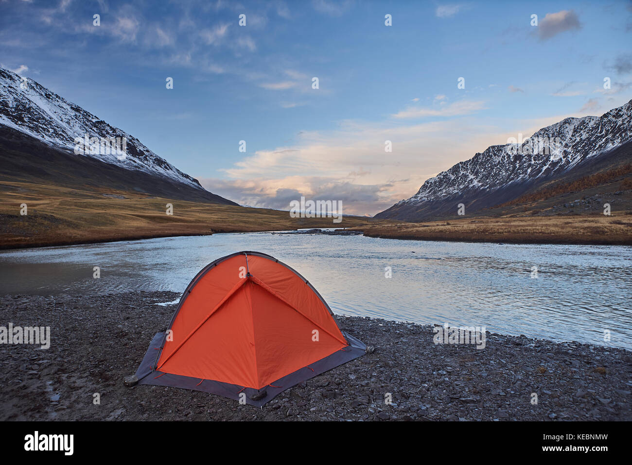 Campsite and an orange tent near a river with Snow-capped peaks in the Mountains - Stock Image
