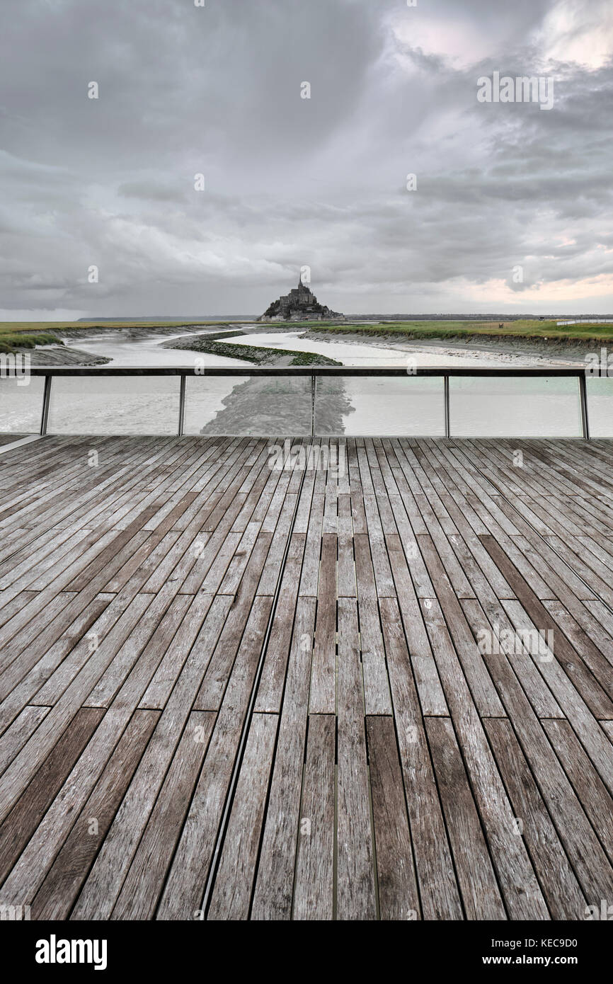 A distant view of Mont Saint Michel and storm clouds from the river Couesnon barrage in Normandy France Stock Photo