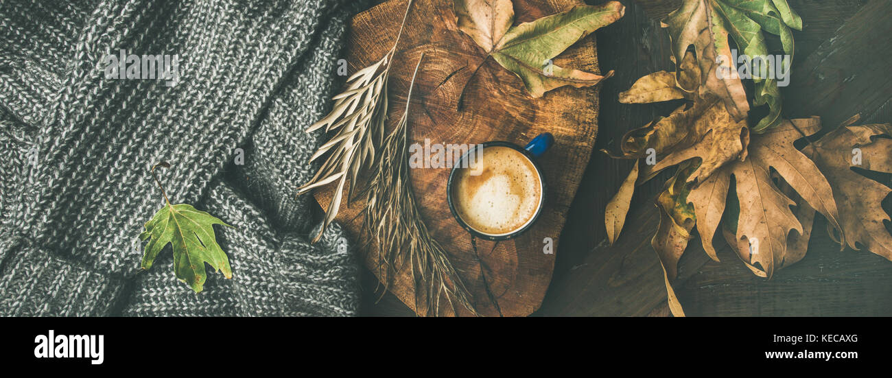 Autumn coffee concept with leaves and grey sweater, wide composition - Stock Image