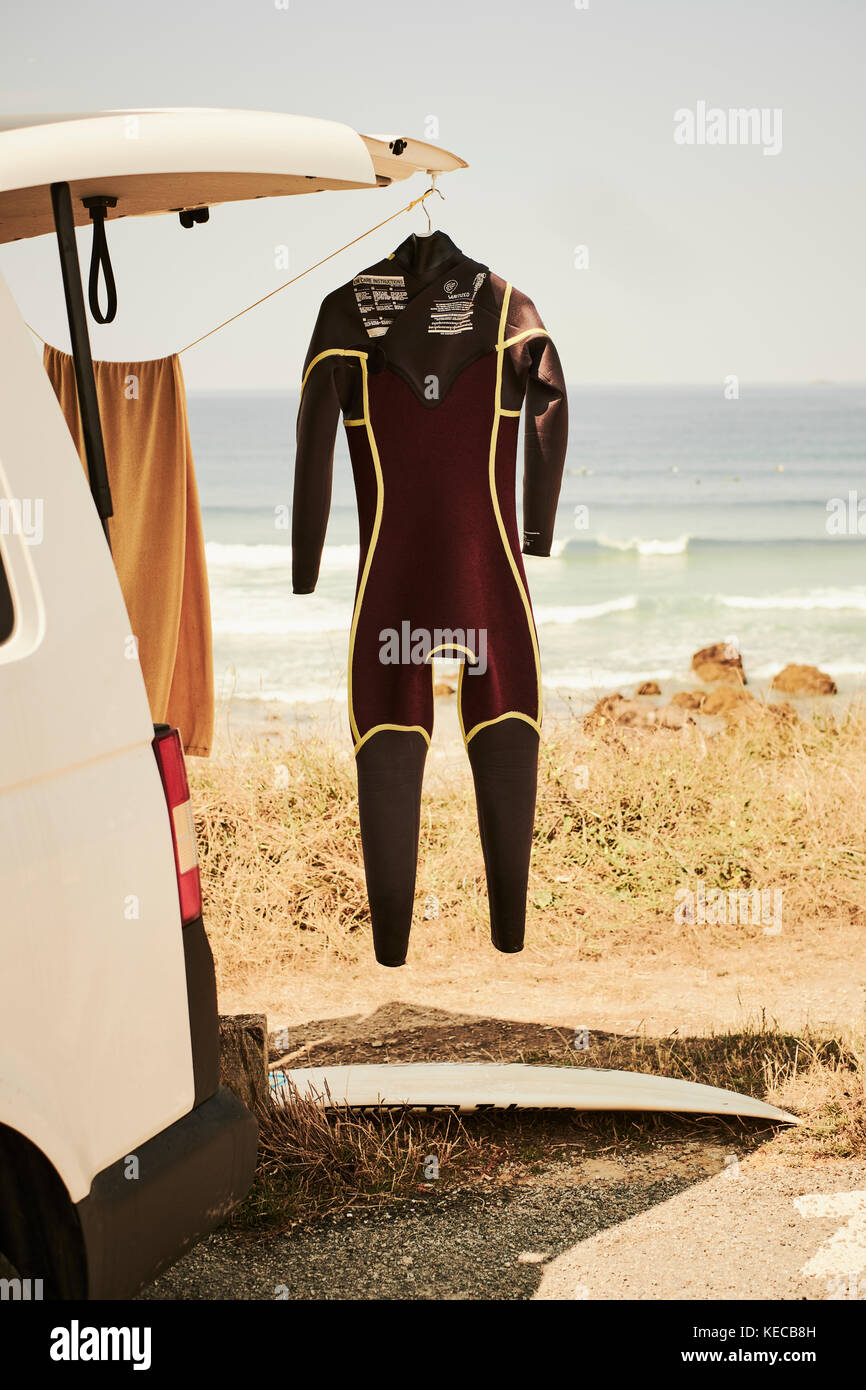A surfers van parked at the beach with a wetsuit hanging outside. Stock Photo