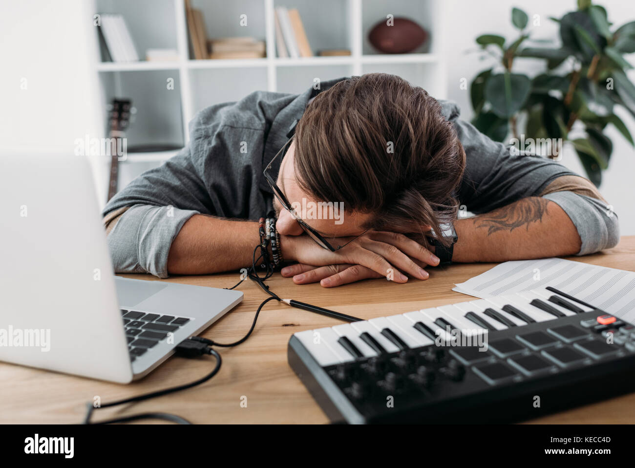 overworked musician sleeping at workplace - Stock Image