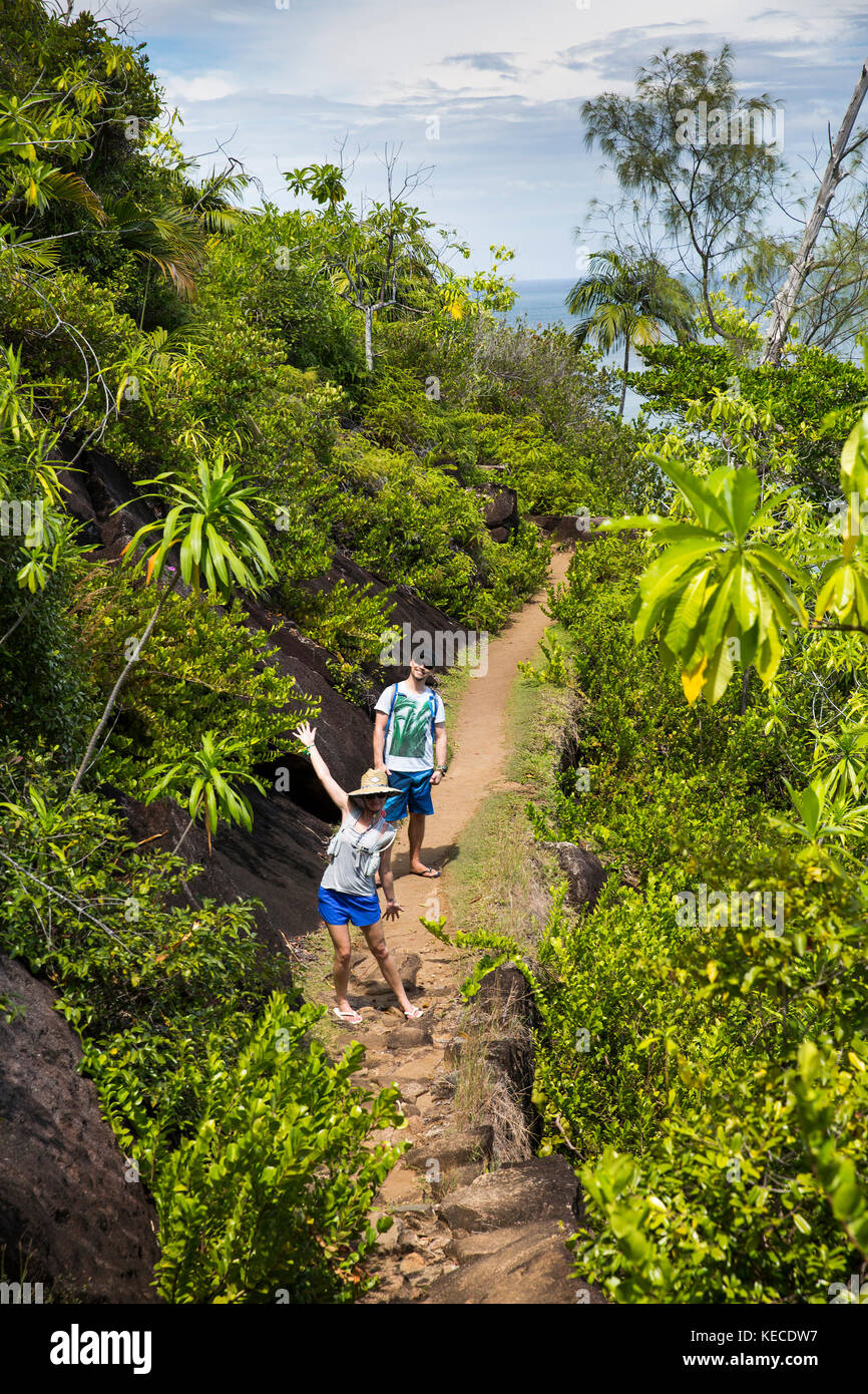 The Seychelles, Mahe, Bel Ombre, Anse Jasmin Estate, tourists walking on trail to Anse Major beach - Stock Image