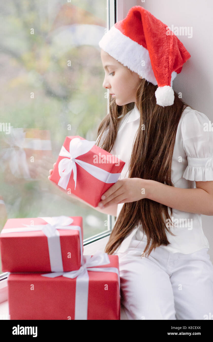e44df552d6131 adorable little girl in Santa hat dreaming by the window holding a box with  gift in Christmas Eve