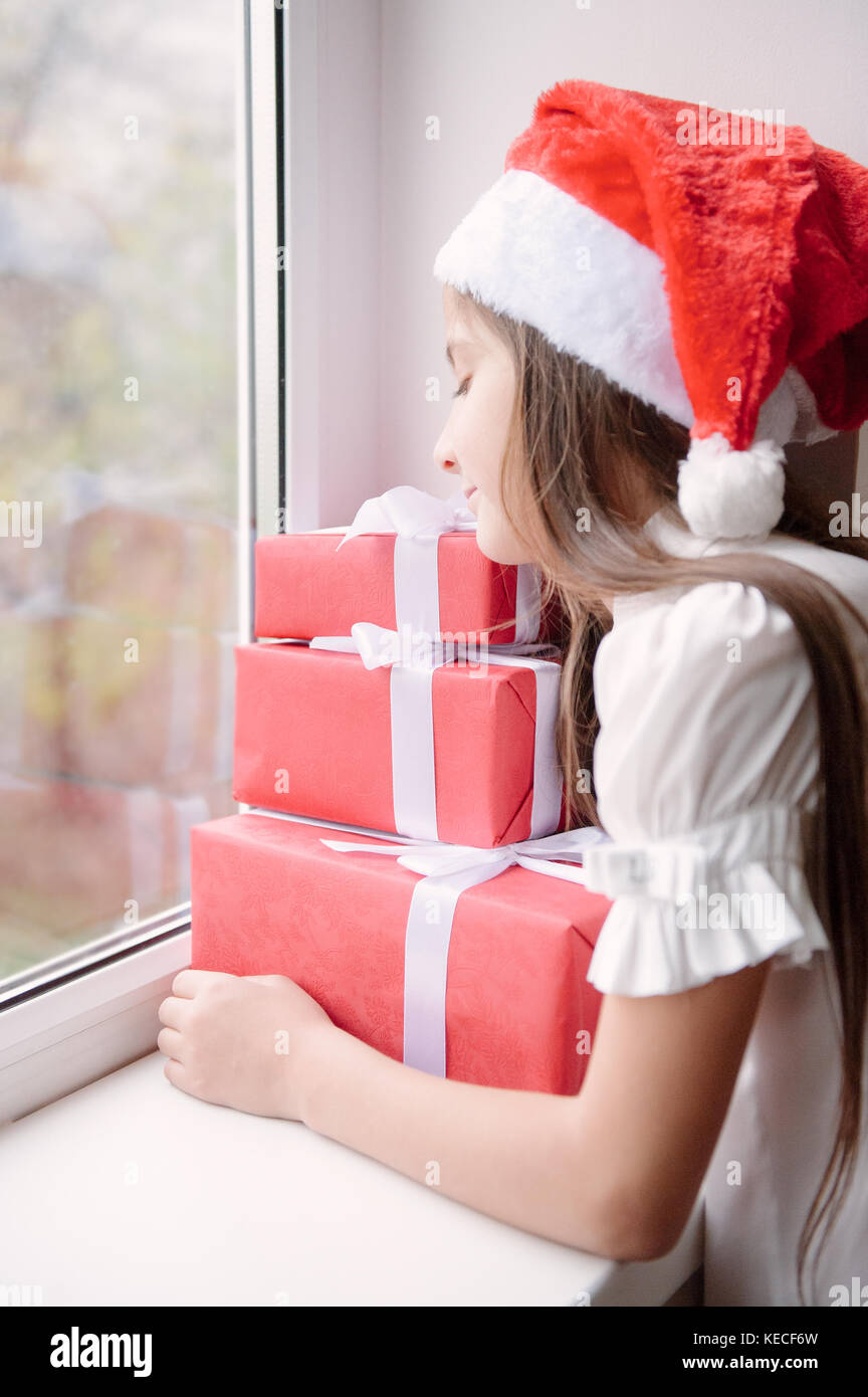 ca34085cb4b11 nice little girl in santa hat dreaming by the window hugging Christmas gifts