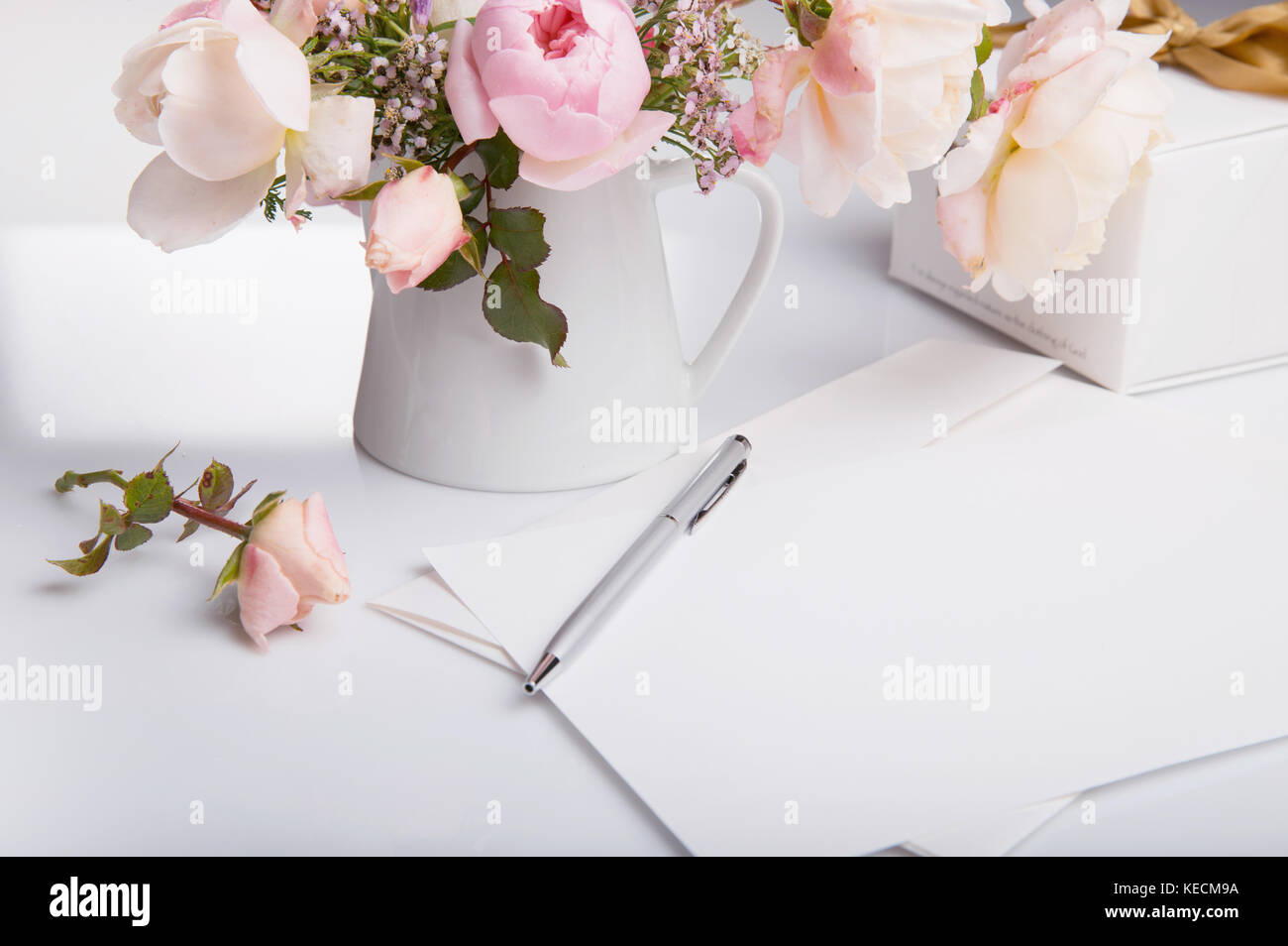 Flat lay shot of letter and white envelope on white background with pink english rose. Invitation cards or love - Stock Image