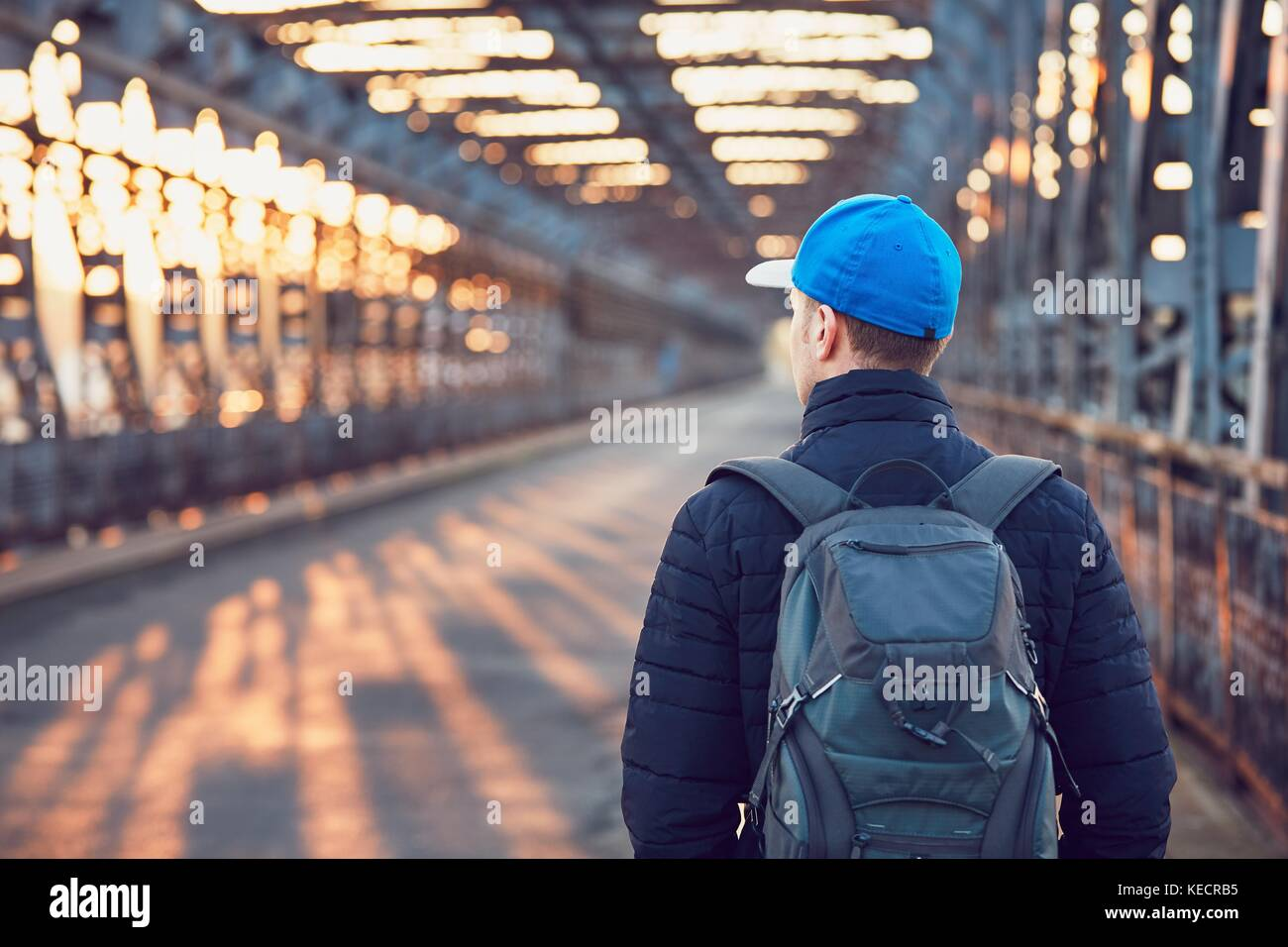 Tourist with backpack walking on the old iron bridge over river at the sunrise. - Stock Image