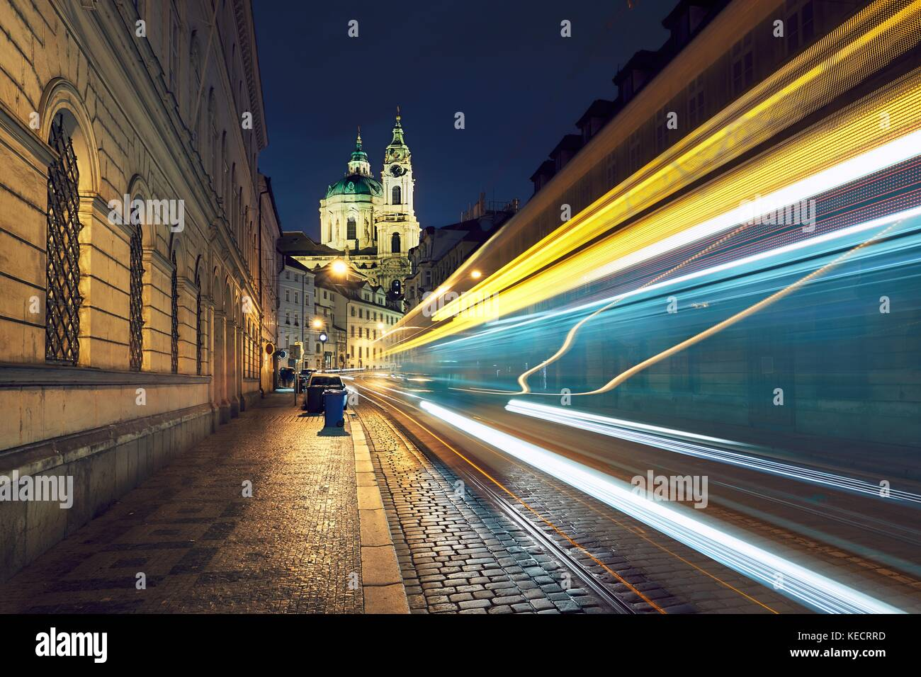 Night traffic on the ancient street near The Church of Saint Nicholas in Prague, Czech Republic. - Stock Image