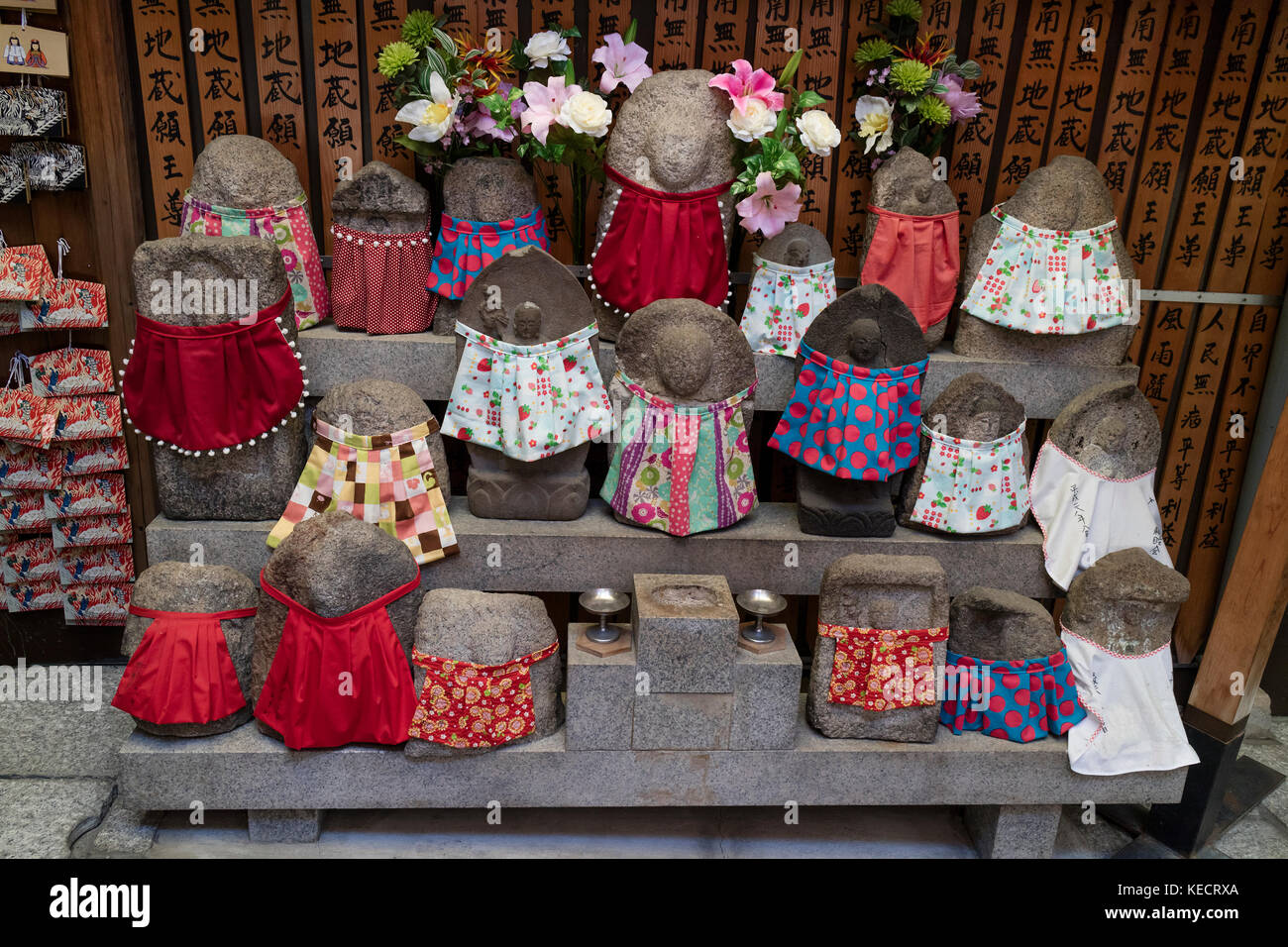 Kyoto - Japan, May 22, 2017: Traditional stone carved Jizo with different colored skirts in front of the temple - Stock Image