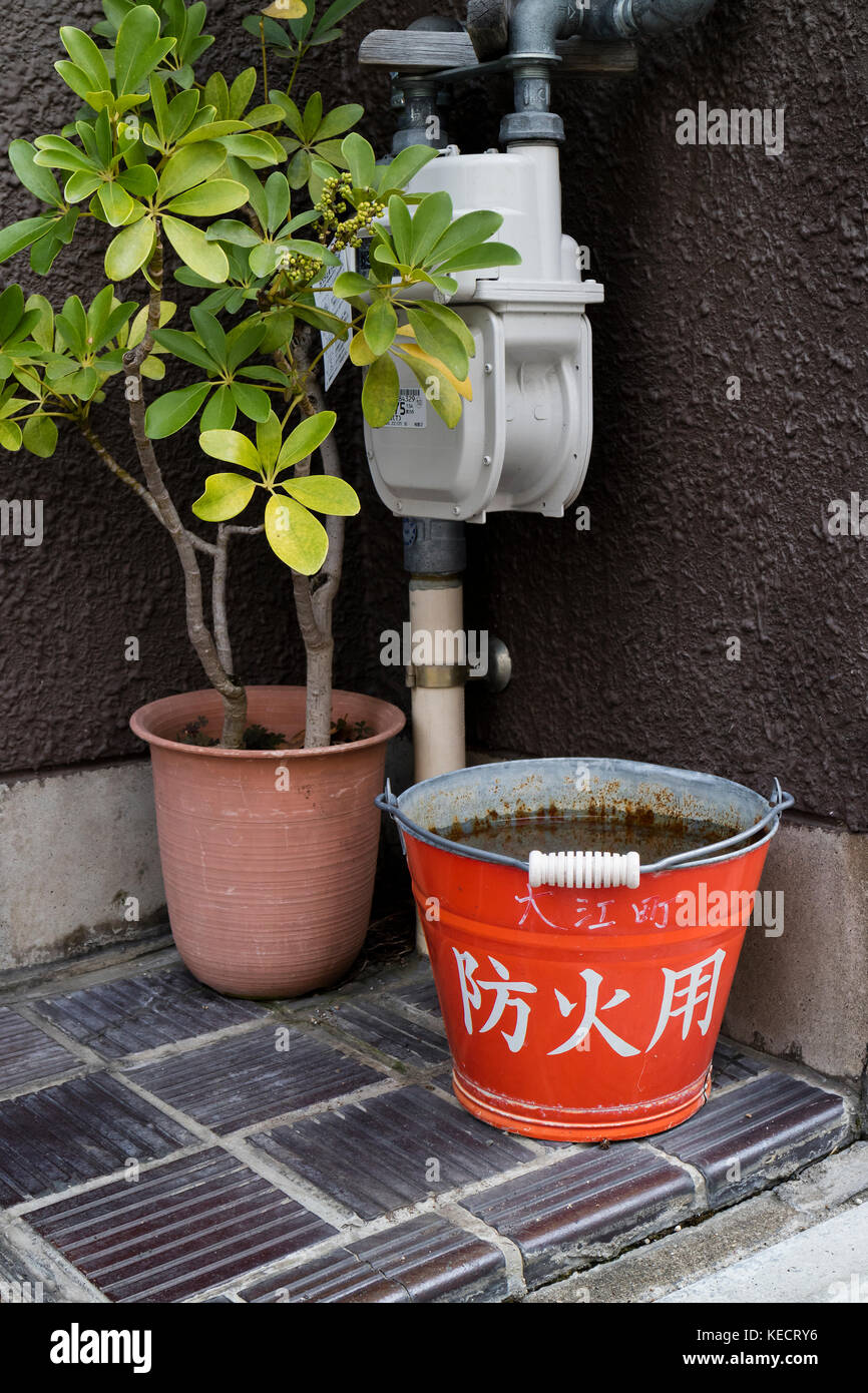 Kyoto, Japan -  May 23, 2017: Traditional red fire bucket with water in front of the house as fire prevention in - Stock Image