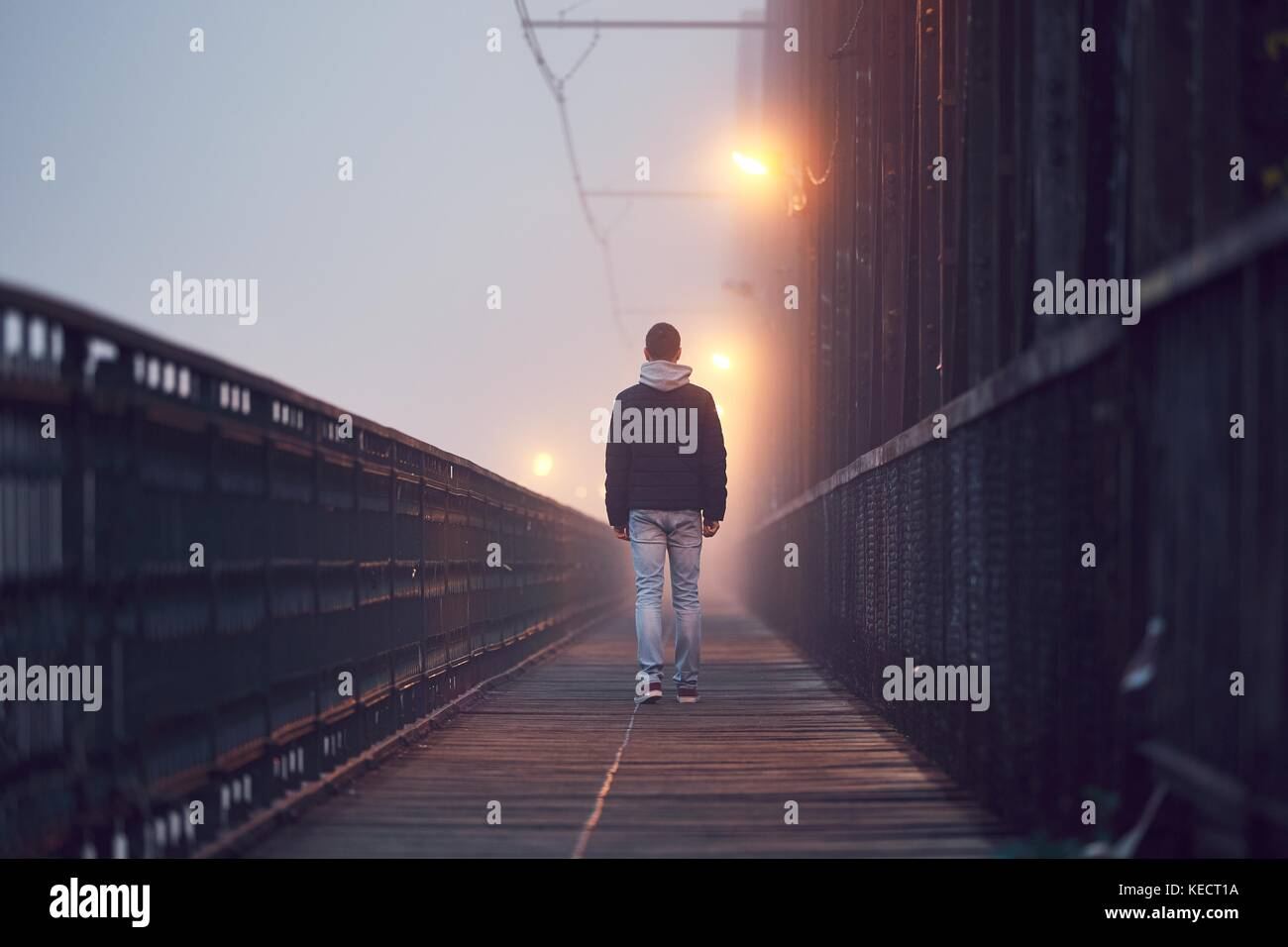 Gloomy weather. Lonely man is walking on the old bridge in mysterious fog. - Stock Image