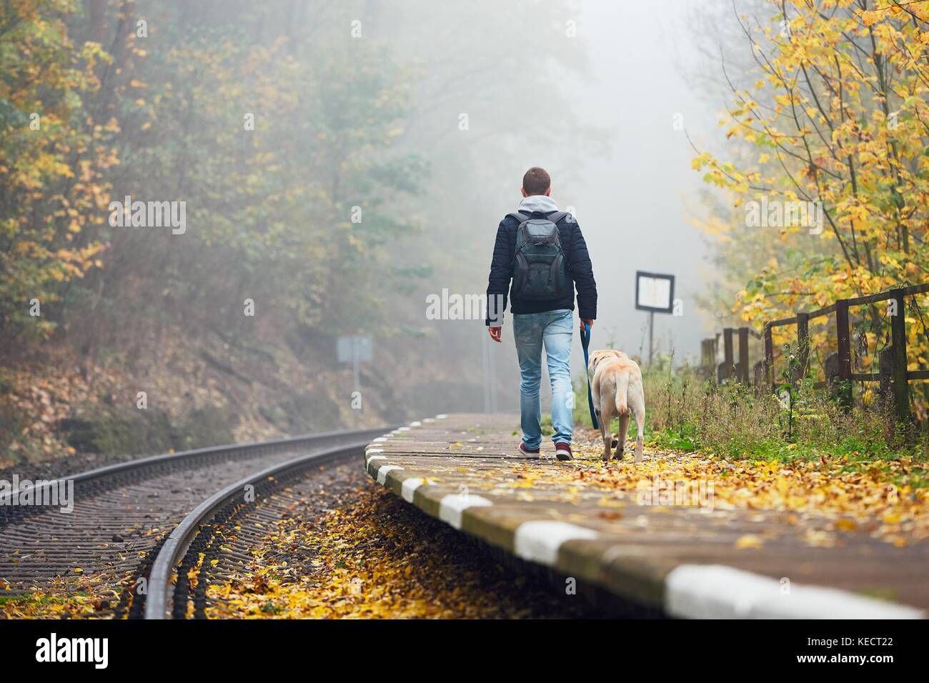 Old railway station in fog. Autumn mood on the trip. Young man traveling with his dog by train. - Stock Image