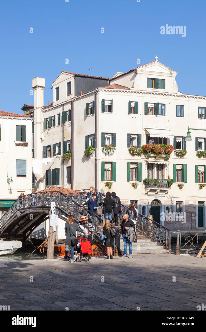 Gondolier and tourists on Ponte de Gheto Novo, Cannaregio, Venice, Italy in the Jewish ghetto on Campo de gheto - Stock Image