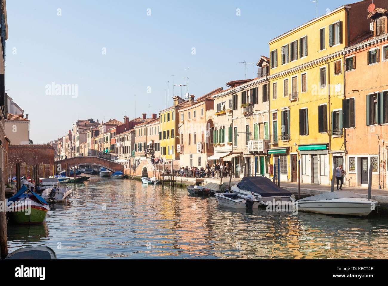Evening light on Fondamenta Ormisini, Cannaregio, Venice, italy with reflections in the water and locals and tourists - Stock Image