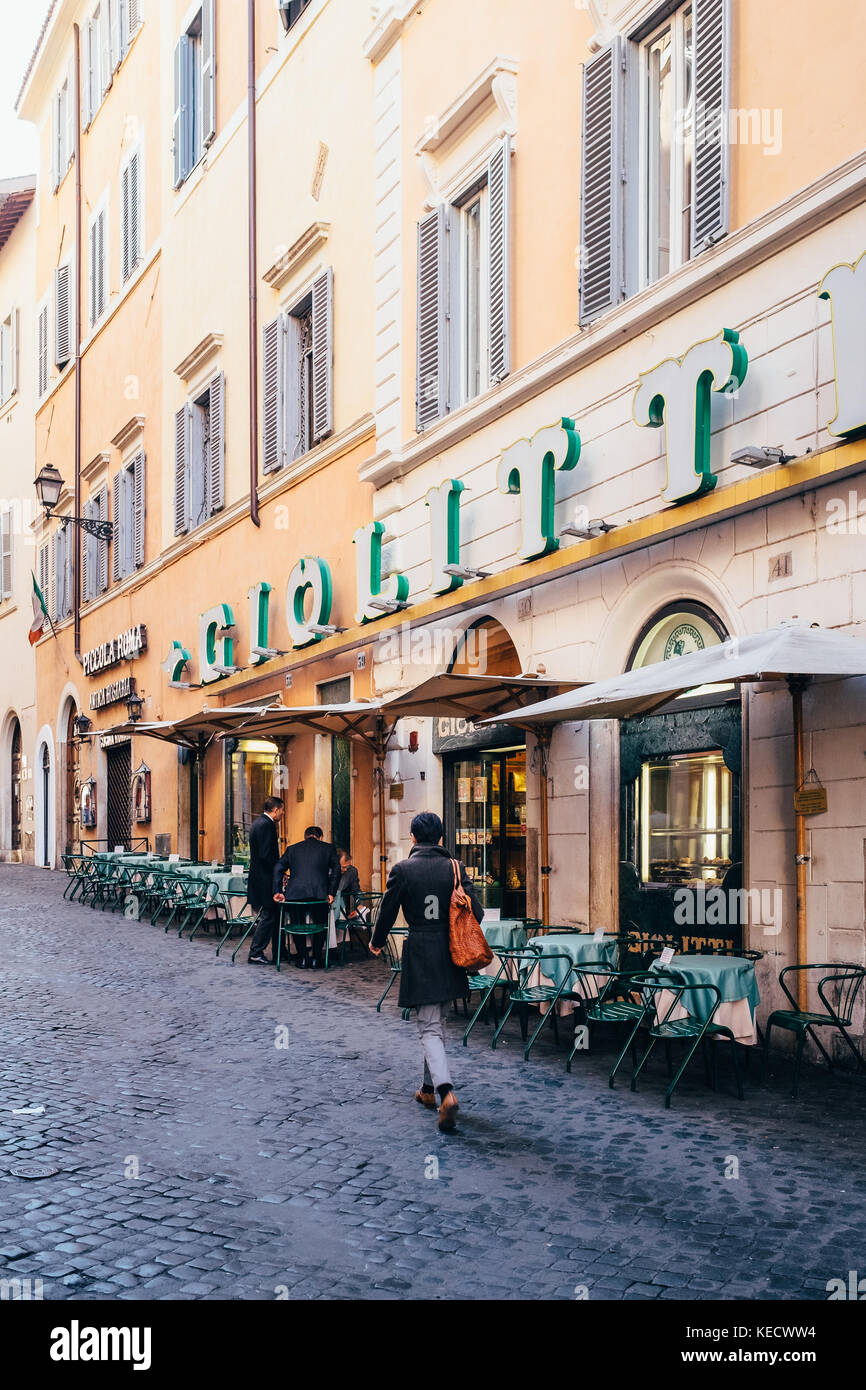 Business people walk to work and pause to meet at the famous Giolitti gelateria and cafe in the early morning hours - Stock Image