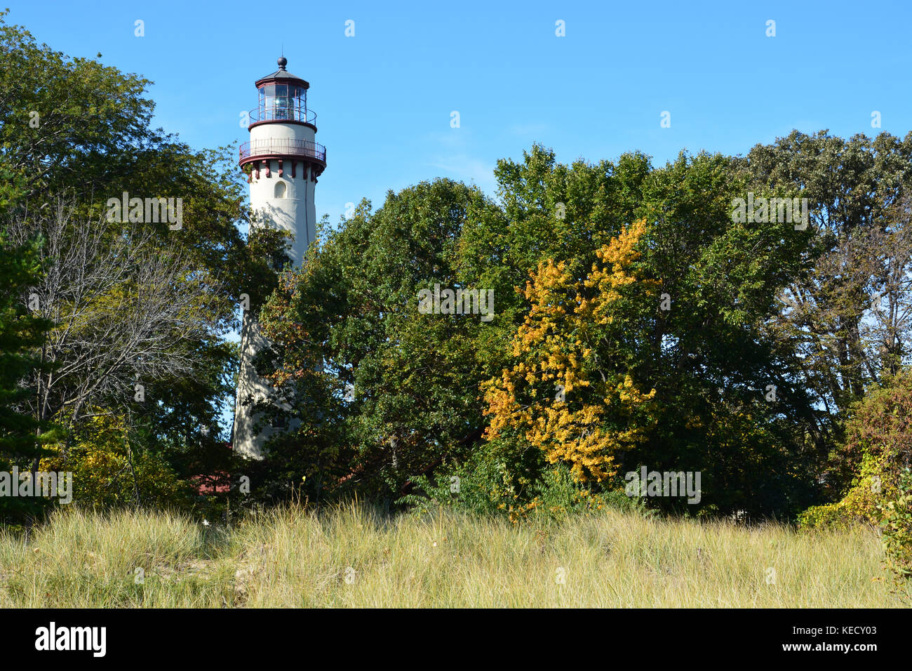The tower rises above the trees at the Grosse Point Light Station on the shoreline of Lake Michigan in Evanston - Stock Image