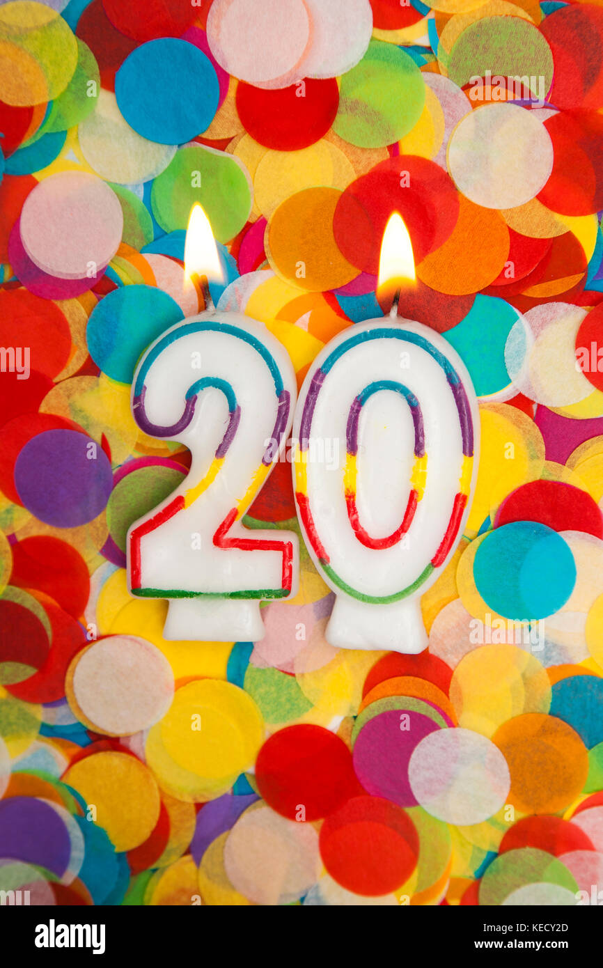 Celebration candle number 20 on a confetti background - Stock Image