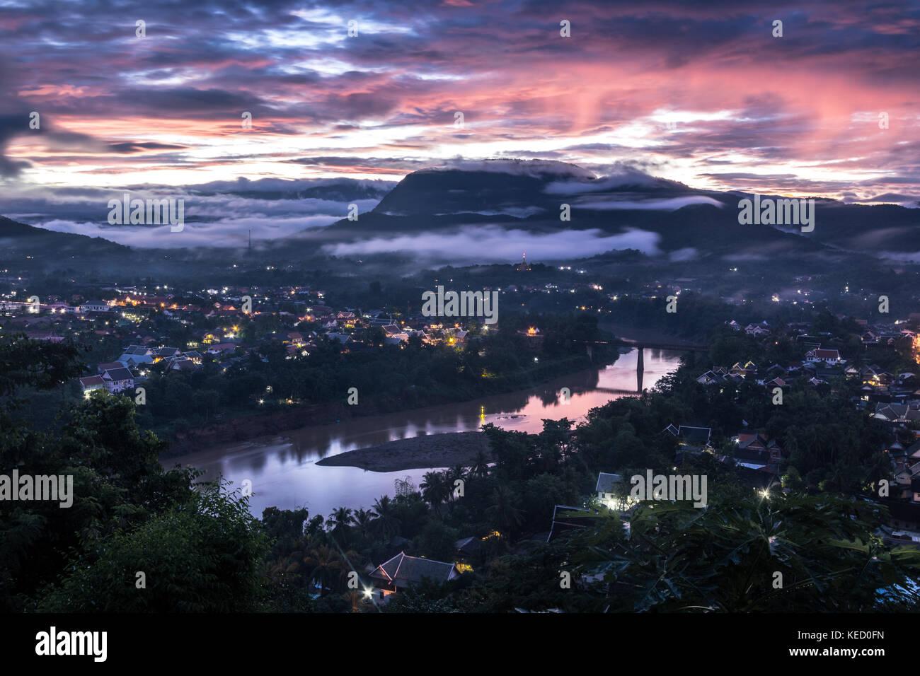 Sun beginning to rise over Luang Prabang, Northern Laos. Stock Photo