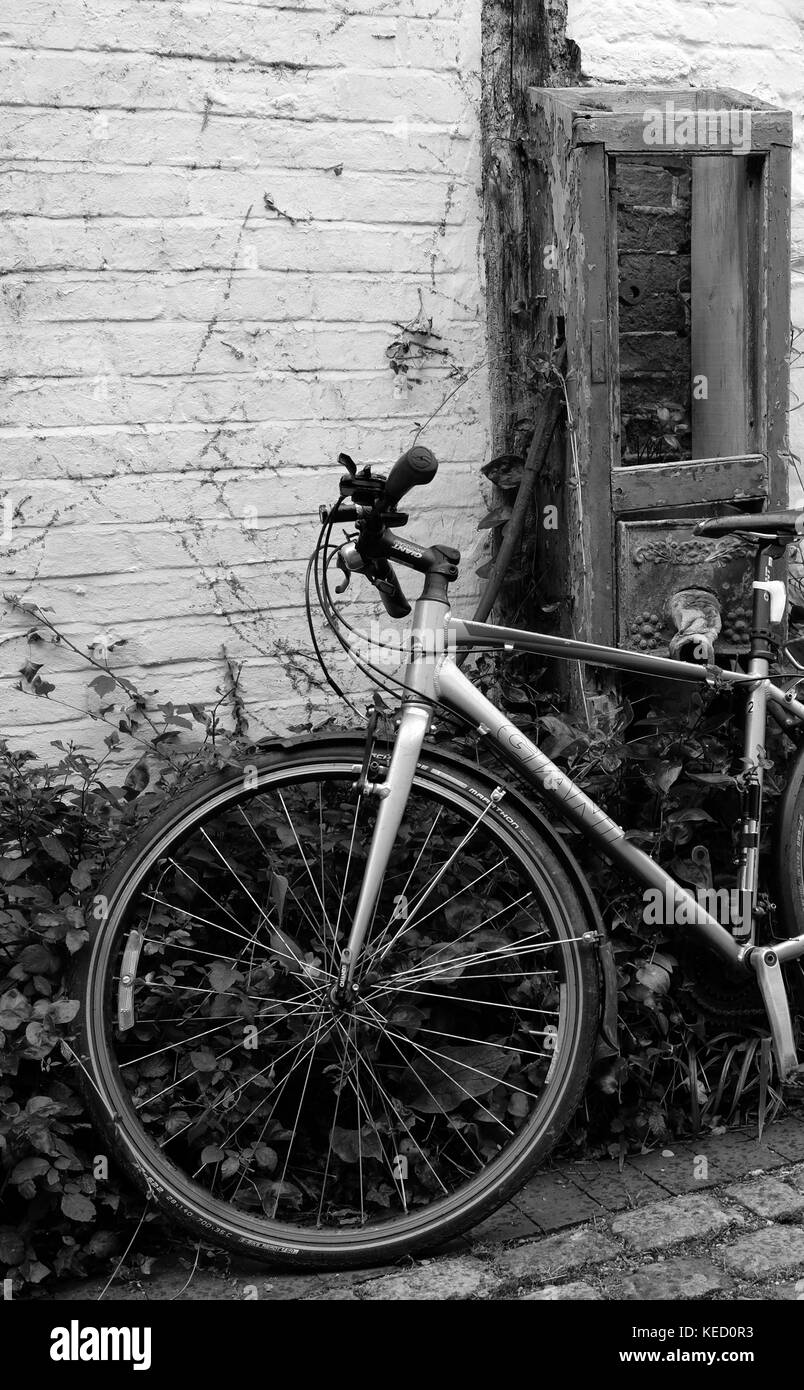 June 2017 - Modern bike bicycle left leaning against an old wall in Thame, Oxfordshire, England. - Stock Image