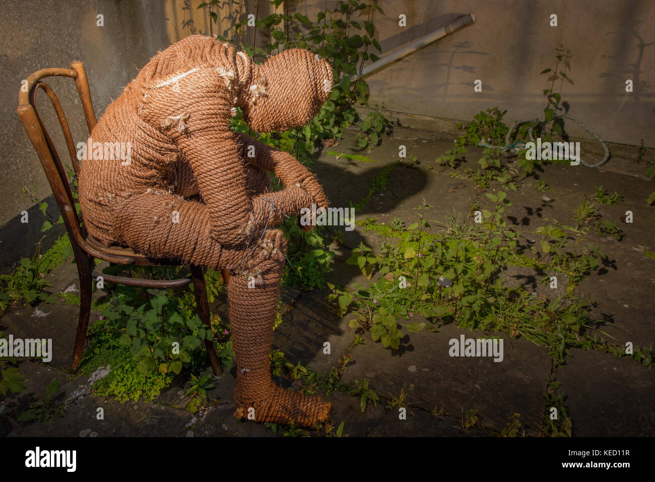 A figure made of rope sitting on a chair in a weedy concrete garden. - Stock Image