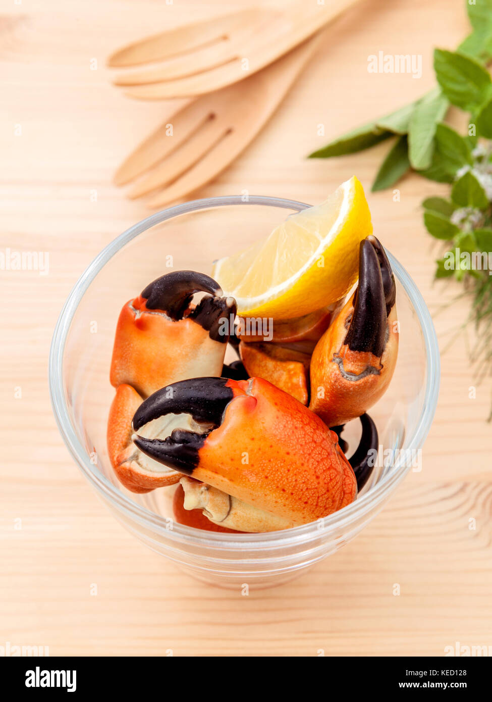 Fresh steamed red crabs leg in glass bowl . Red crabs leg with ingredients. Steamed red crabs leg with herbs Fennel - Stock Image