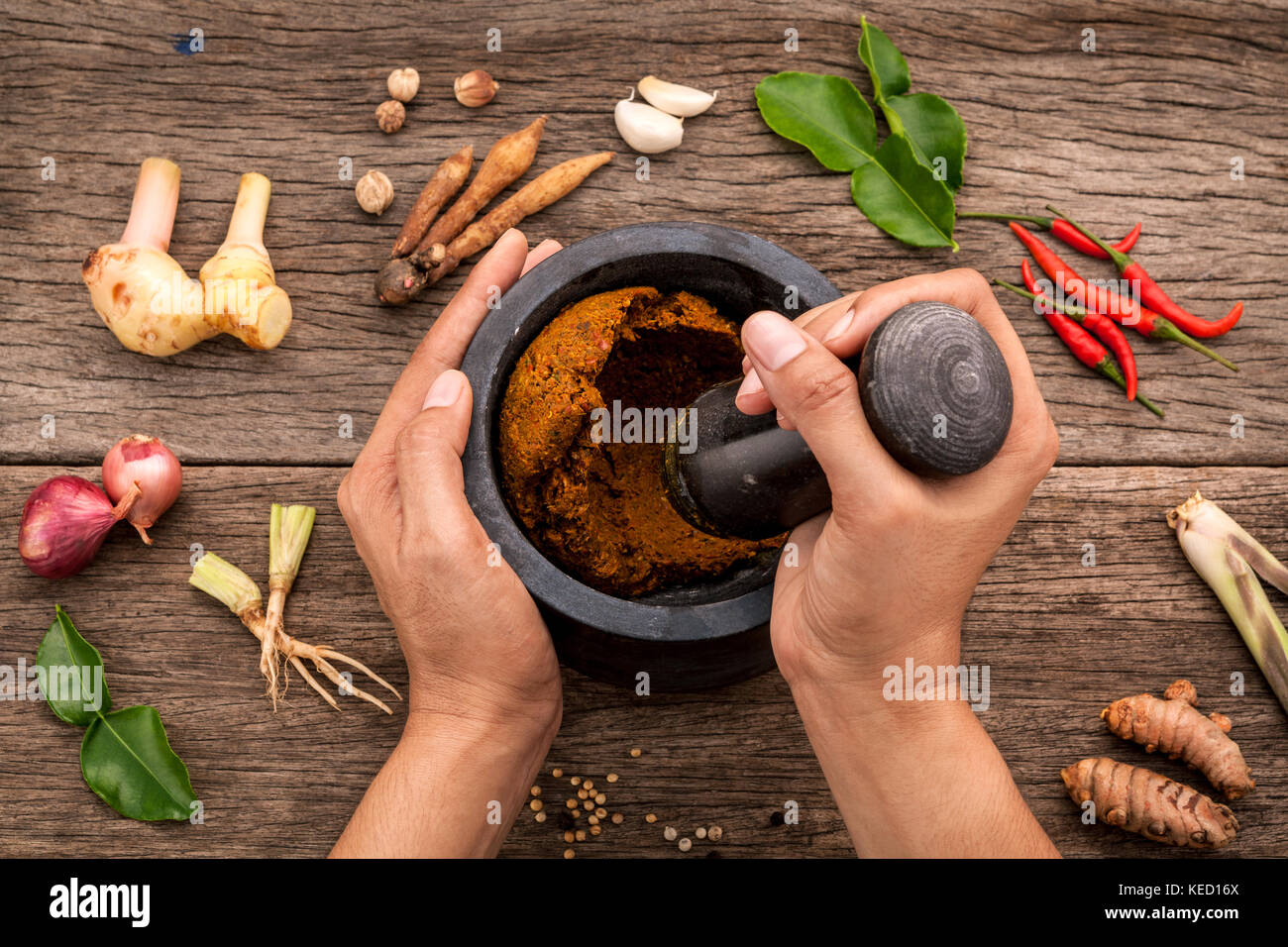 The Women hold pestle with mortar and spice red curry paste ingredient of thai popular food on rustic wooden background. - Stock Image