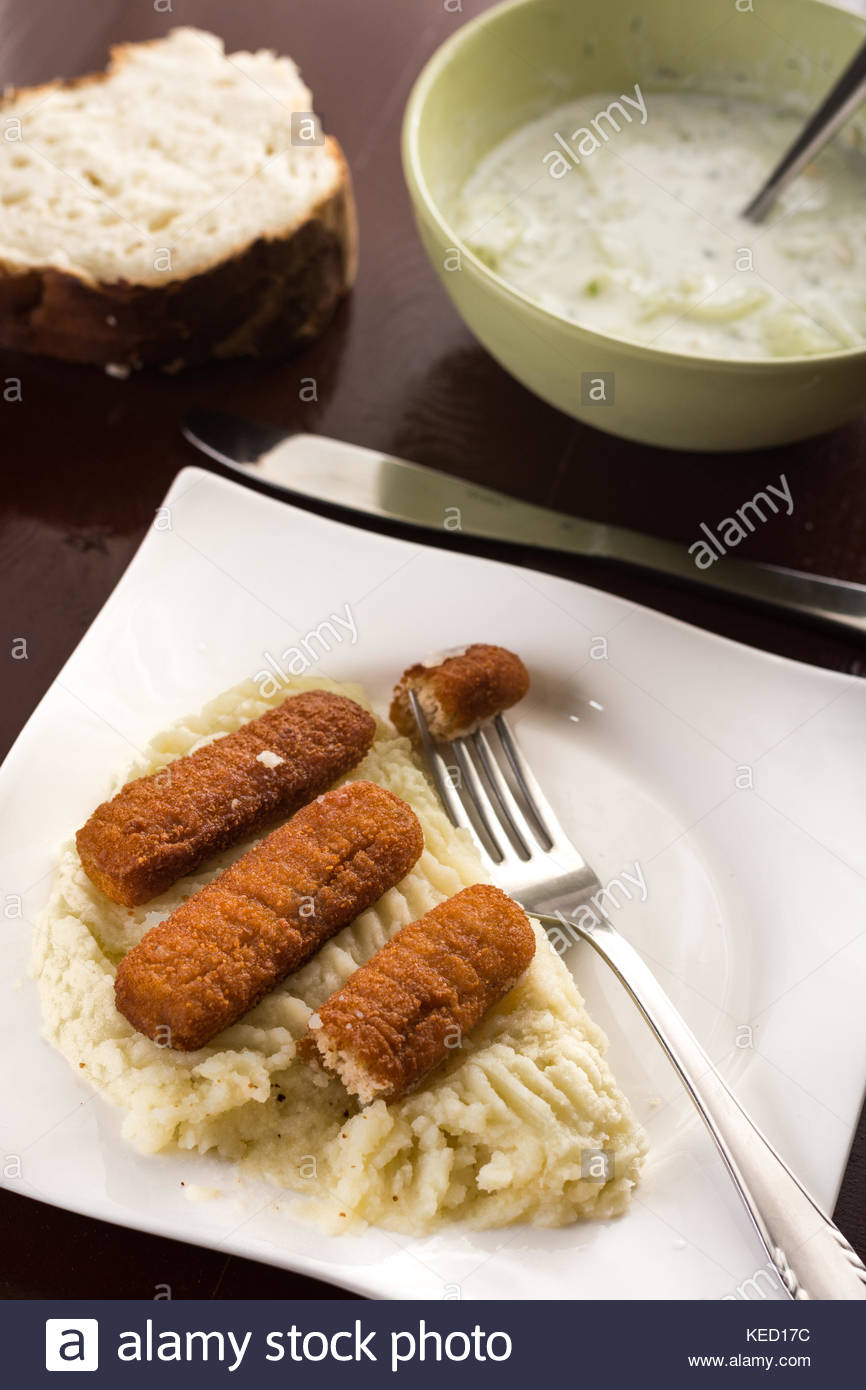 Fish sticks with mashed potatoes and cucumber salad on the table. - Stock Image