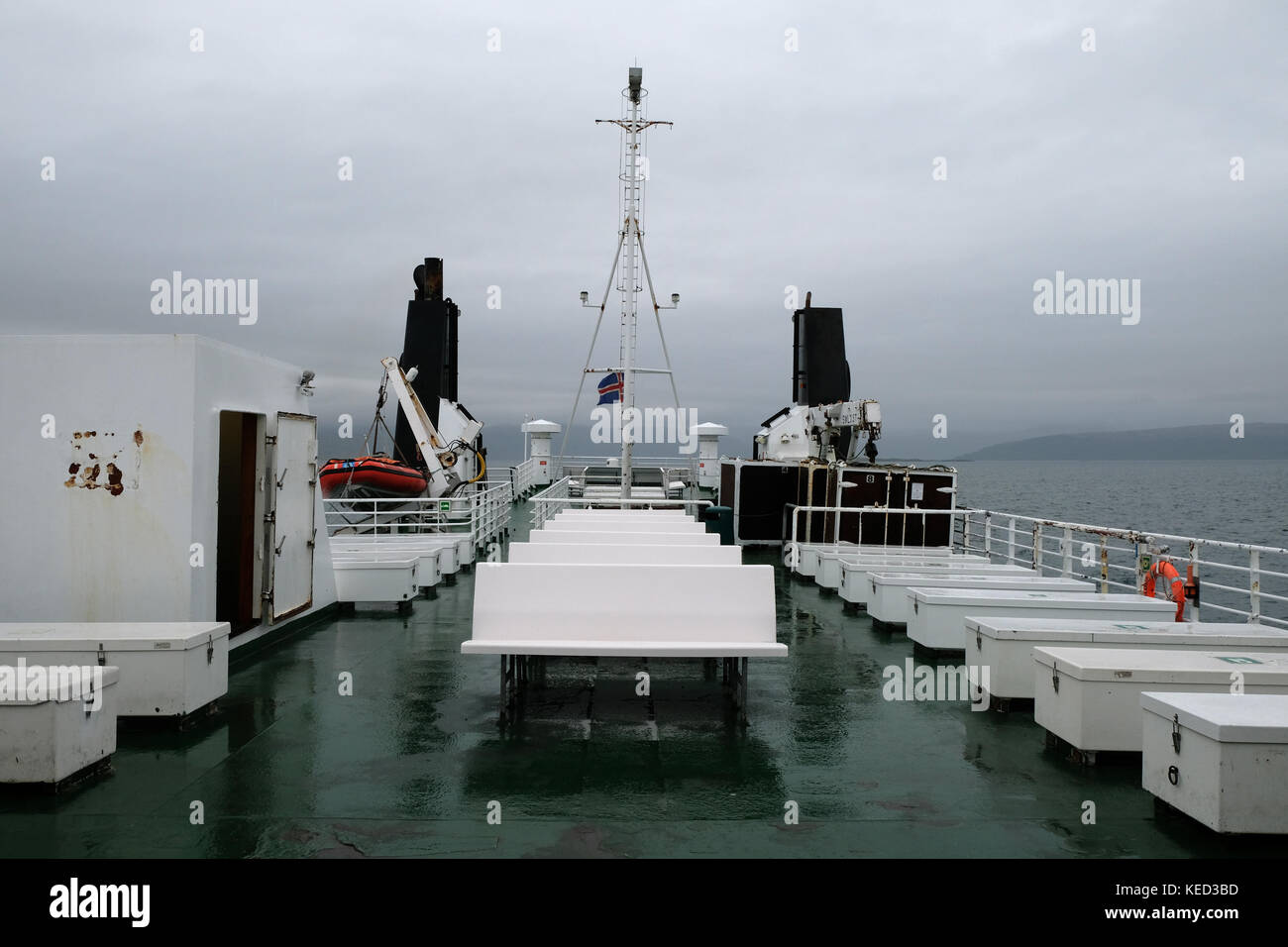 View from rear or stern of Baldur car ferry passenger chairs, seats and life boat on overcast day at sea flying - Stock Image