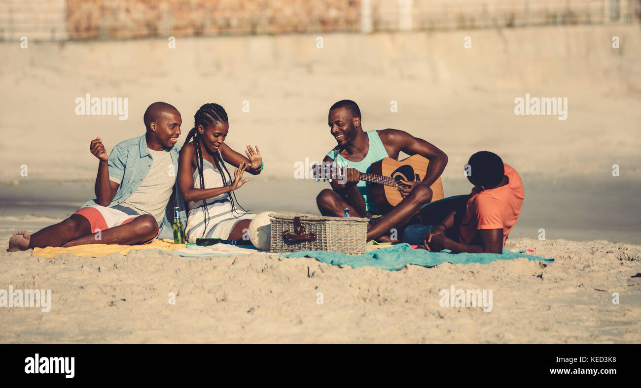 Group of young people hanging out at the beach. Young afro american man playing guitar for friends. Stock Photo