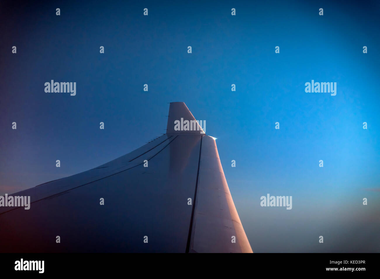 Airplane wing at sunrise. - Stock Image