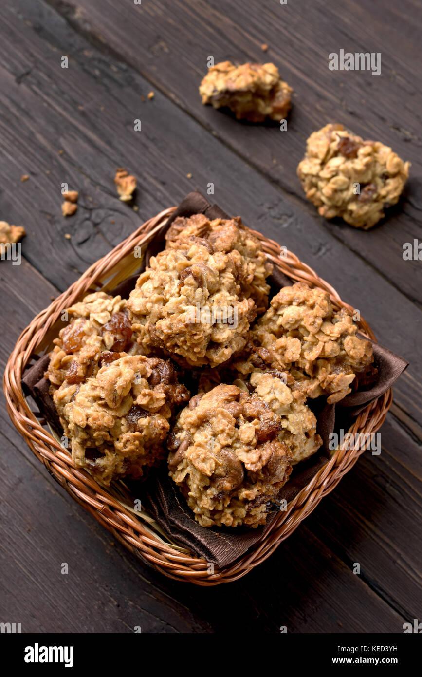 Healthy oats cookies in wicker basket over wooden background, top view - Stock Image