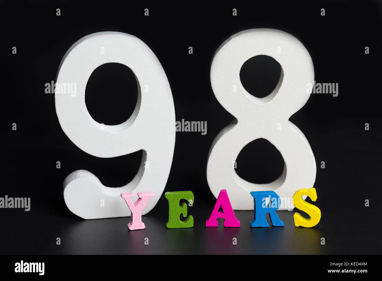 Letters and numbers ninety-eight years on a black isolated background. - Stock Image