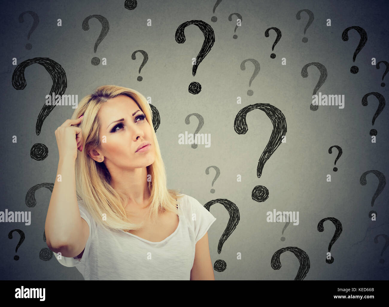 Portrait confused thinking woman bewildered scratching head seeks a solution looking up at many question marks isolated Stock Photo
