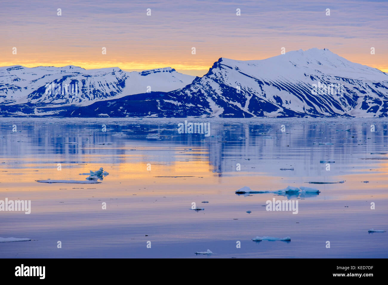 Offshore view to mountains reflected in calm sea on east coast in arctic summer evening sunshine. Spitsbergen, Svalbard, - Stock Image