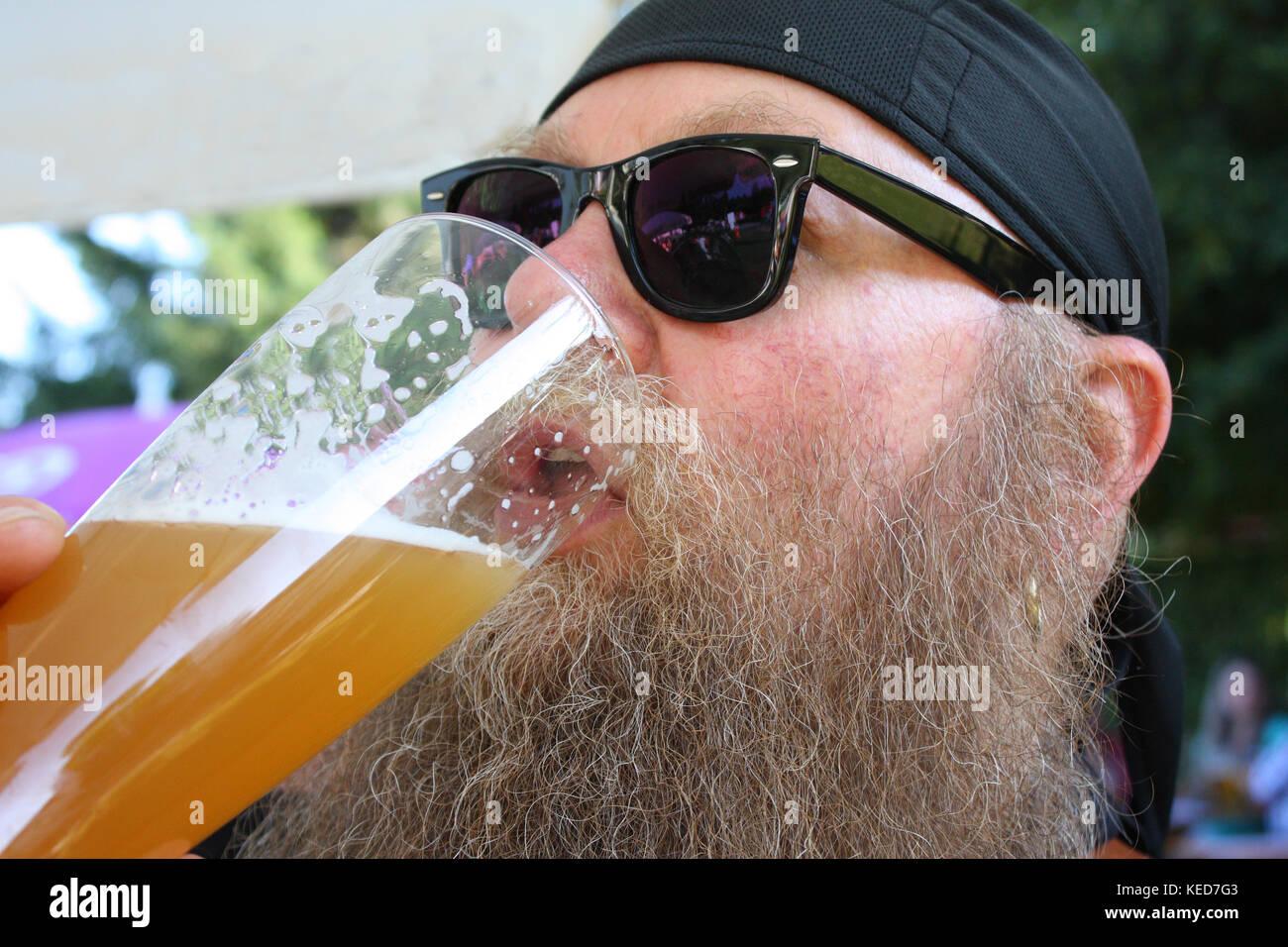 Mann mit langem Bart drinkt ein Bier - Stock Image