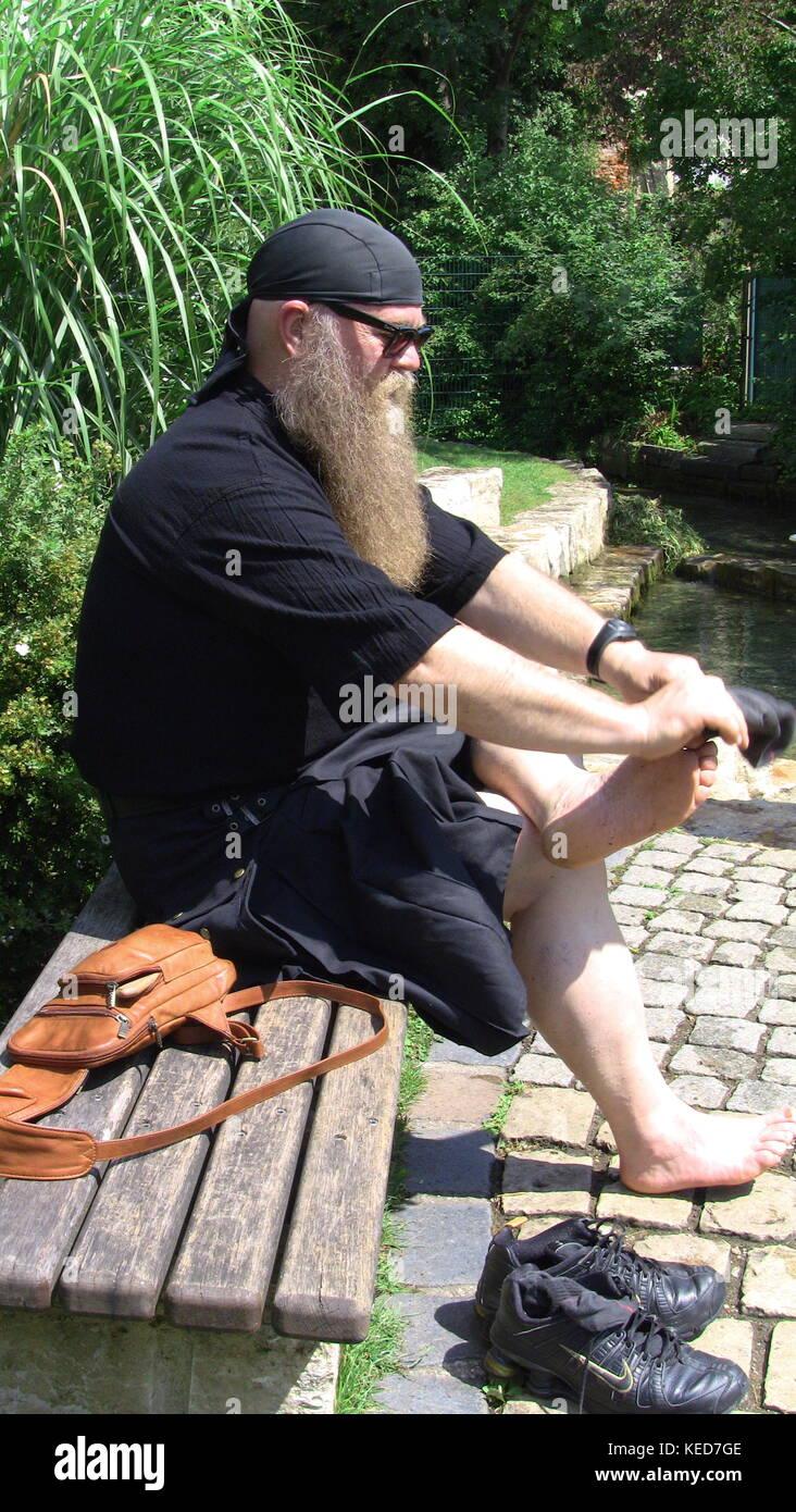 Mann mit Bart und Schottenrock ziehrt sich seine Socken an - Stock Image