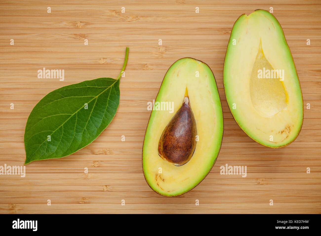 Healthy food concept. Closeup ripe avocado with avocado leaves on wooden background. Halved organic avocado with - Stock Image