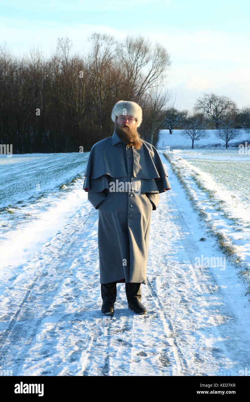 Mann mit langem Bart und Mantel geht im Schnee spazieren - Stock Image