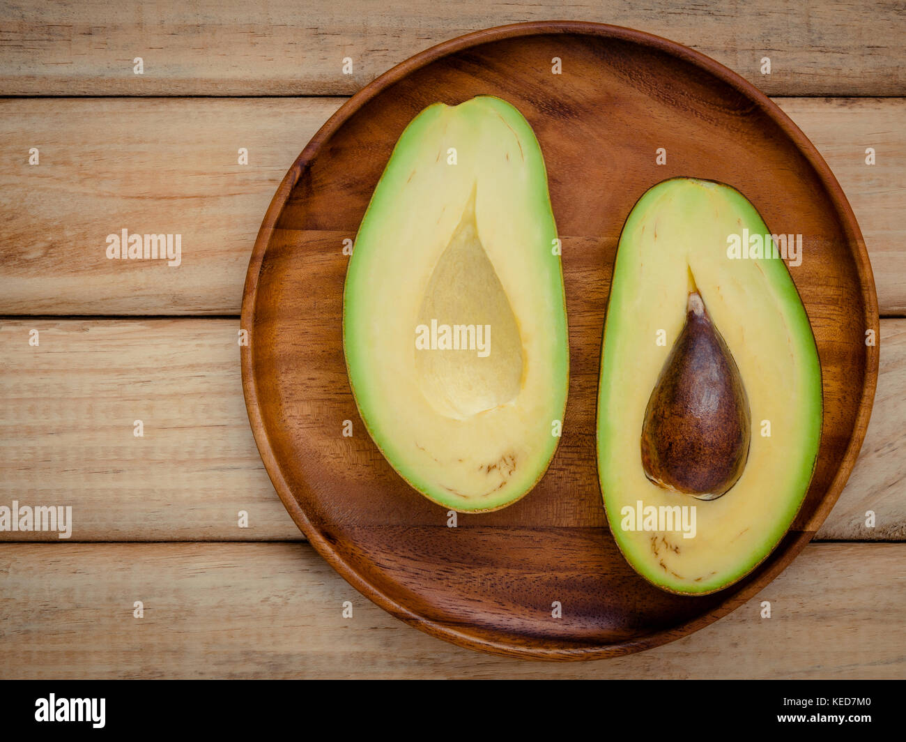 Healthy food concept.Closeup ripe avocado on wooden background. Halved organic avocado with core on wooden background. - Stock Image